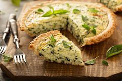 Spinach and herb Florentine quiche. On a cutting board for breakfast royalty free stock photos