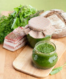 Spinach with herbs milled in the pot. On a wooden board with bacon and bread Royalty Free Stock Photo