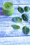 Spinach juice and spinach leafs side view Royalty Free Stock Images