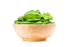 Spinach leaf in wooden bowl isolated on white background Stock Images