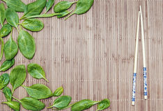 Spinach leaves on a bamboo mat and bamboo chopsticks Royalty Free Stock Images