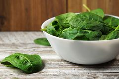 Spinach Leaves Bowl On Rustic Table royalty free stock images
