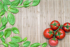 Spinach leaves and branch of ripe tomatoes on a bamboo mat Royalty Free Stock Image