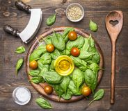Spinach leaves have been laid out around a circular chopping board, with herbs and salad spoon,knife and salad, salt, pepper, che. Spinach leaves have been laid Stock Photos