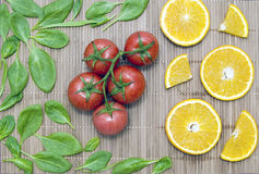 Spinach leaves, orange slice, a bunch of tomatoes on a bamboo ma Stock Photos