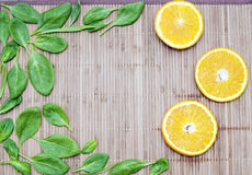 Spinach leaves and orange slices on a bamboo mat Stock Image