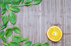 Spinach leaves and orange slices on a bamboo mat Stock Photos