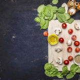 Spinach leaves and sliced mushrooms, laid out on a cutting board with herbs and cherry tomatoes on wooden rustic background top vi Stock Images