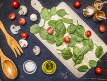 Spinach leaves and sliced mushrooms, laid out on a cutting board with herbs and cherry tomatoes on wooden rustic background top vi Royalty Free Stock Photography