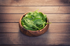 Spinach leaves in a wooden plate Stock Image