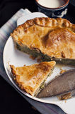 Spinach mushroom pie. Vegetarian spinach mushroom pie in casserole with cup of fresh milk Royalty Free Stock Photography