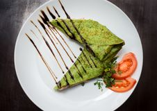 Spinach Pancake with a tomato. Green spinach pancakes with a tomato and soy sauce on a white plate Royalty Free Stock Image
