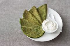 Spinach pancakes with cottage cheese sauce. On a white plate on a gray background, free space. Delicious healthy breakfast Stock Photos
