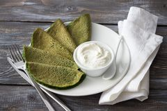 Spinach pancakes with cottage cheese sauce. On a white plate on a wooden table. Delicious healthy breakfast Royalty Free Stock Image