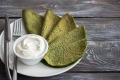 Spinach pancakes with cottage cheese sauce. On a white plate on a wooden table, free space. Delicious healthy breakfast Stock Image
