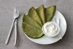 Spinach pancakes with cottage cheese sauce. On a white plate on a gray background. Delicious healthy breakfast Royalty Free Stock Photography