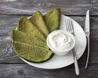 Spinach pancakes with cottage cheese sauce. On a white plate on a wooden table. Delicious healthy breakfast Royalty Free Stock Photos