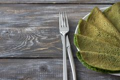 Spinach pancakes on a white plate. On a wooden table, free space, selective focus. Delicious healthy breakfast Stock Photo