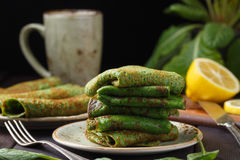 Spinach pancakes on wood table. Spinach pancakes on dark wooden table with tea cup Stock Photos