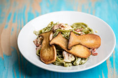 Spinach pasta with mushrooms. A plate of green spinach fettucini pasta with creamy sauce and fried king oyster mushroom slices Stock Photo