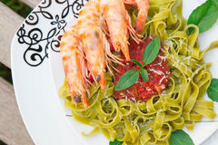 Spinach pasta with shrimps and tomato sauce Stock Photo