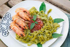 Spinach pasta with shrimps and tomato sauce Royalty Free Stock Image