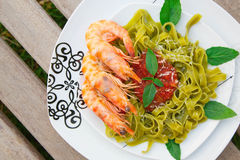 Spinach pasta with shrimps and tomato sauce Stock Images
