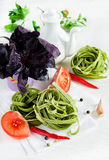 Spinach pasta with tomatoes, herbs and spices Royalty Free Stock Images