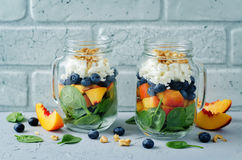 Spinach peach blueberry goat cheese walnuts salad in a jar. Toning. selective focus royalty free stock image