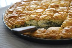 Spinach pie in pieces. Traditional greek spinach pie in pan Stock Photos