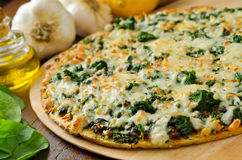 Spinach Pizza. A freshly baked thin crust spinach pizza with garlic, lemons, and olive oil Stock Photography