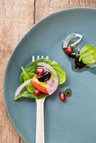 Spinach and Pomegranate salad on yellow fork Royalty Free Stock Images