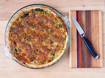 Spinach Quiche. Image of a spinach quiche cooling on a cutting board Stock Photos