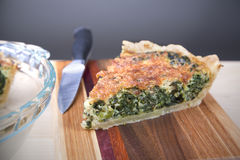Spinach Quiche. Closeup of a slice of spinach quiche on a cutting board Stock Images