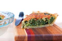 Spinach Quiche. Closeup of a slice of spinach quiche on a cutting board against white background Stock Images