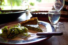 Spinach quiche and salad eaten outdoors on sunny day. A meal served al fresco in a covered porch area. In the background, bright sun shows that it's a hot, sunny Stock Images