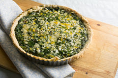 Spinach quiche and vegetables with melted cheese stock image