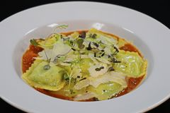 Spinach and ricotta cheese ravioli with saffron tomato sauce stock image