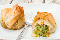 Spinach and ricotta filo pastry parcels. Two spinach and ricotta filo pastry parcels.  Crisp and flaky filo pastry that has been brushed with butter for a golden Royalty Free Stock Images
