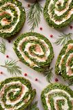 Spinach roulade stuffed with cream cheese and smoked salmon sliced on a white background. Top view Stock Photo