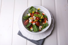Spinach salad with cherry tomatoes and corn in bowl, white wooden table Stock Images
