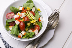 Spinach salad with cherry tomatoes and corn in bowl, white wooden table Stock Photography