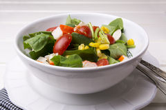 Spinach salad with cherry tomatoes and corn in bowl, white wooden table Stock Photo