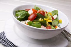Spinach salad with cherry tomatoes and corn in bowl, white wooden table Stock Photos