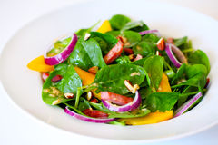 Spinach salad with mango, ham, onion and almonds Stock Photos