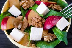 The spinach salad with nuts and apples served on table Stock Image