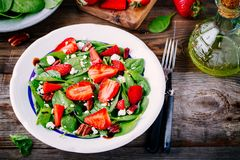 Spinach salad with strawberries, goat cheese, balsamic and walnuts Stock Photo