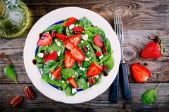 Spinach salad with strawberries, goat cheese, balsamic and walnuts. On wooden background royalty free stock photography