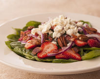 Spinach salad with strawberries and goat cheese. Fresh salad of spinach and strawberries, topped with goat cheese Stock Photography