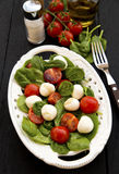 Caprese salad with spinach. Tomato, mozzarella and spinach salad Royalty Free Stock Photos
